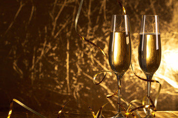 Two glasses of champagne in golden tone with copy space.