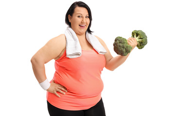 Overweight woman exercising with a broccoli dumbbell