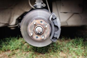 Broken rusty brake discs on the car on the Jack. Steel brake pads