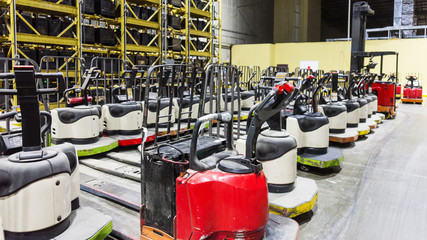 Forklifts or pallet jacks in a warehouse with batteries on racks