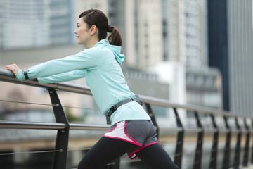ジョギング姿でストレッチをする女性