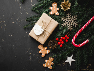 Christmas background with gingerbread, xmas tree and decoration on dark wooden board.