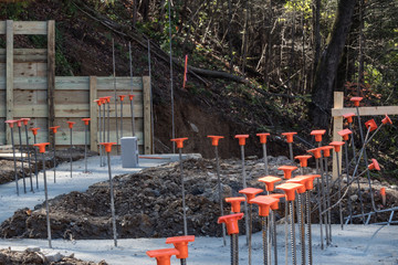 Construction site on hillside with footings poured and rebar with orange safety caps, horizontal aspect