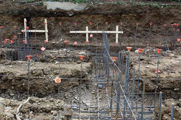 Construction site view of steel rebar foundation framework with orange caps, horizontal aspect