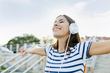 Happy young woman wearin headphones enjoying the summer