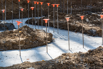 Construction site with rebar in poured footings for a building, horizontal aspect
