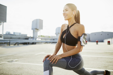 Smiling young woman wearing earphones stretching before jogging