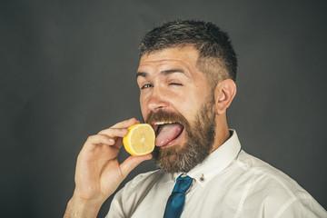 man with long beard lick lemon fruit on black background