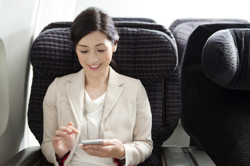 Businesswoman using phone on plane