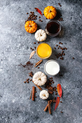 Ingredients for cook spicy pumpkin latte. Glasses with black coffee, pumpkin milk, cream with spices, coffee beans, autumn leaves above over gray texture background. Top view, space.