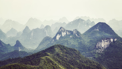 Retro toned picture of karst formations landscape around Guilin on a foggy day. It is one of China most popular tourist destinations.