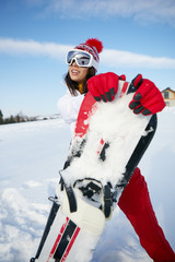 Sporty female holds snowboard in mountains