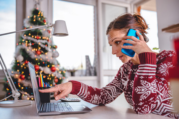 Woman talking on smart phone at home office