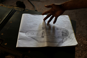 Master boat builder Ali Skanda, 44, shows a sketch of his project of building a traditional sailing dhow entirely out of recycled plastic on the island of Lamu