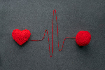 Handmade red yarn ball with heart made of red wool yarn and thread like ECG pattern on a gray woolen fabric background. Red warm heart like a symbol of love. Heart health, heartbeat, love concept