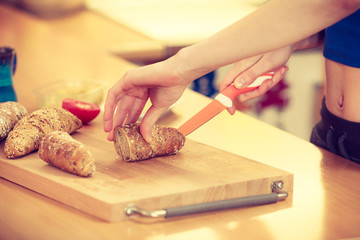 Woman making sandwich cutting bread