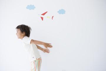 飛行機の絵と翼を真似る男の子