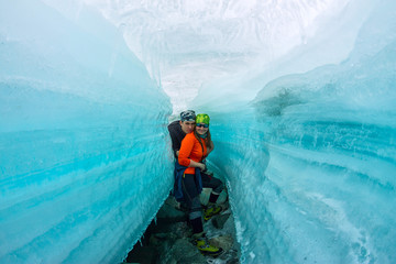 Female and man inside the crack in the ice glaciers Iceland.