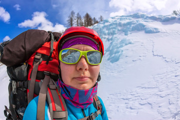 portrait female mountaineer with backpack, helmet and harness with climbing in mountain