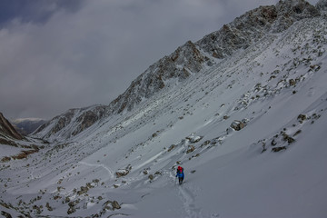 Female mountaineer with backpack, helmet and harness with climbing in mountain