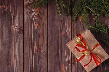Christmas gift boxes and fir tree  on wooden background.