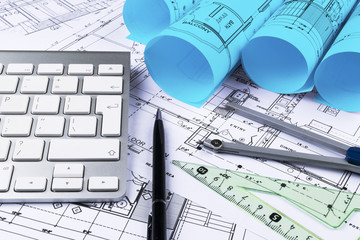 Architectural drawings of the modern house with computer keyboard. Architectural blueprints and blueprint rolls and a drawing instruments on the worktable. Drawing compass, plans.