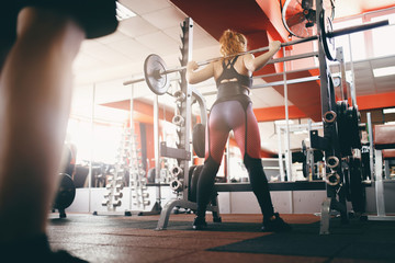 Barbell. Girl lifts  bar, makes squat in gym. Concept of workout