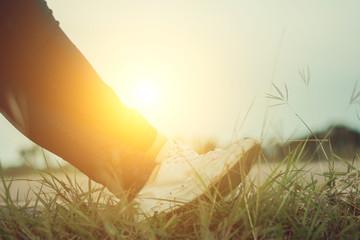Legs of girl relax on sunset.