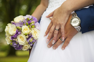 Detail on hands of just married young couple with rings, watches and flowers. Outside in nature