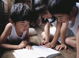 読書する日本人の3人の子ども