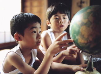 地球儀を眺める2人の日本人の男の子