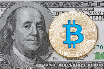 Golden cryptocurrency blue bitcoin on hundred dollar banknote background.