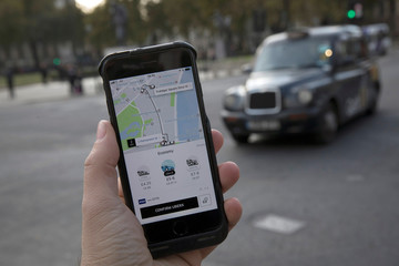 A photo illustration shows the Uber app on a mobile telephone, as it is held up for a posed photograph, with a London Taxi in the background, in London