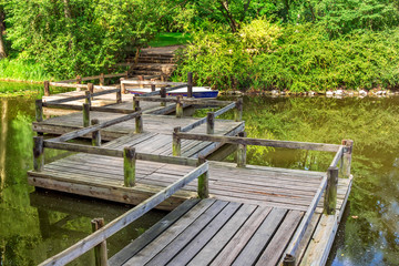 Vintage zigzag shaped wooden bridge and boat on a pond in a park on a sunny summer day.