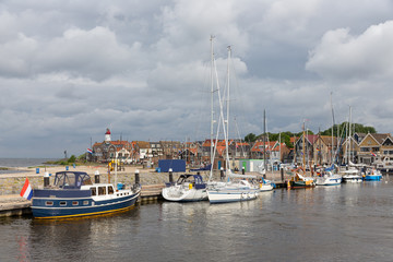 Harbor of historic Dutch village Urk with modern sailing yachts moored to a pier
