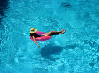 Young beautiful girl is swimming in the pool with a pink circle
