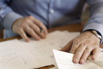 Hands of a businessman making calculations on a paper sheet. Soft background