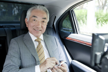 携帯電話を操作する社内の中高年ビジネスマン