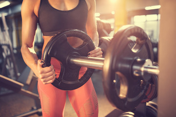 Trainer in gym putting weights on machine, concept