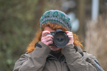 A woman photographed, the camera in focus and the motive in the visor