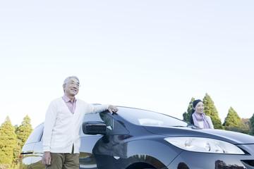 車の横で景色を見るシニアカップル