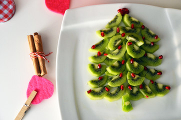 Kiwi and pomegranate Christmas tree New Year background. Healthy dessert idea for kids party