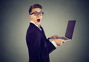 Surprised stunned man with laptop computer looking at camera