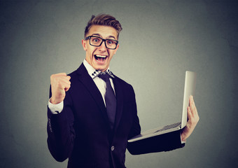 Successful young man using laptop building online business celebrating success. .