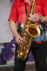 Saxophone player with the saxophone in arms, playing with it.