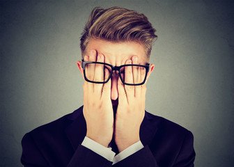 Closeup portrait young man in glasses covering face eyes with both hands