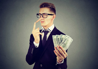 Financial fraud concept. Liar business man in suit and glasses with dollar cash