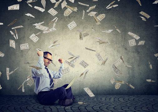 Businessman using a laptop building online business earning money under dollar bills cash rain falling down.