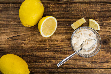 Portion of healthy Lemon powder on an old wooden table (selective focus; close-up shot)