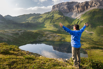 Hiker standing with raised hands near the beautiful mountain lake and enjoying view